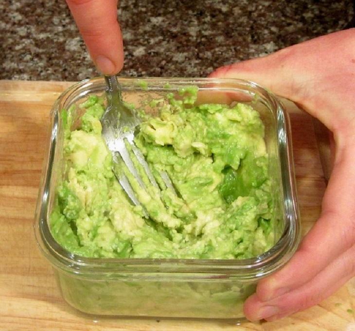 Bạn hãy tách hạt bơ ra, lấy phần thịt cho vào tô hoặc hộp đựng, nghiền nhỏ và thêm một ít nước chanh