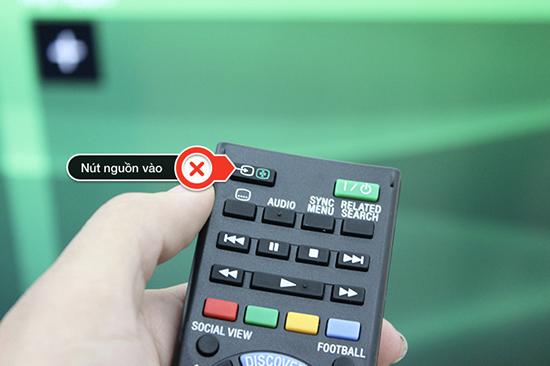 Bấm vào nút nguồn trên điều khiển tivi